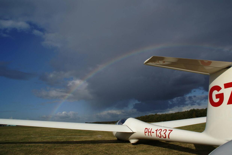zweefvliegtuig met regenboog